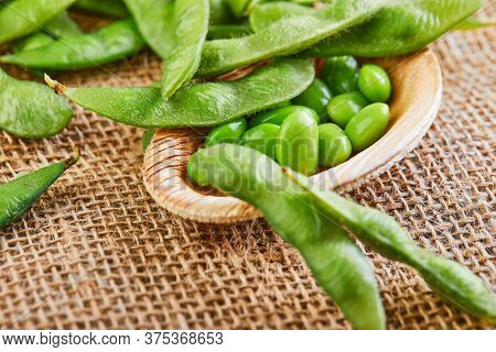Edamame Or Soybeans In A Wooden Plate On A Brown Sackcloth.
