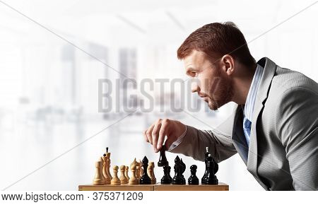 Concentrated Businessman Playing Chess Game. Successful Management And Leadership Concept. Confident
