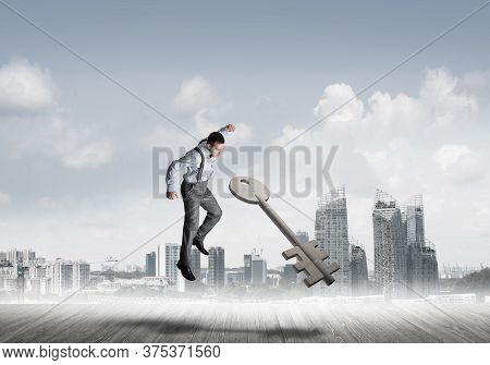 Determined Businessman Against Modern Cityscape Breaking With Fist Stone Key Figure