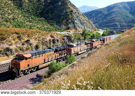 July 7, 2020 In Cajon Pass, Ca:  Bnsf Railroad Engines Transporting Rail Cars With Cargo Northbound