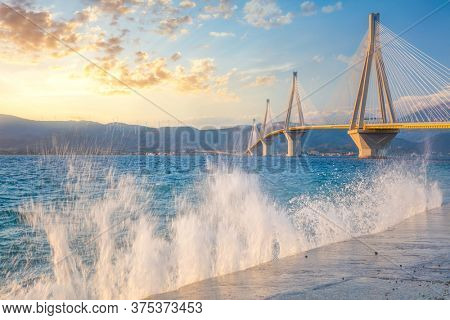 Amazing view - Modern Bridge at the evening sunset time with waves splash. Rion-Antirion Bridge, Greece, Europe. The Rion-Antirion Bridge in Greece one of the world's longest  bridge