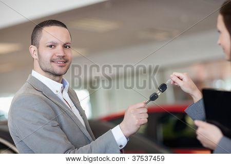 Man holding car keys with a businesswoman in a garage