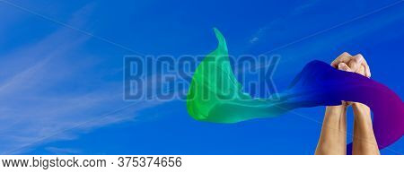 Clasped Hands Of Two Men Surrounded With Rainbow Fabric Flag With Blue Sky Background. Lgbt Concept
