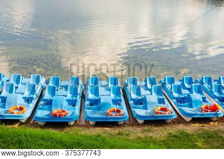 Plastic Rental Pedal Boats Parked On The Lake Shore On A Sunny Day. Active Rest Outdoors. Nobody