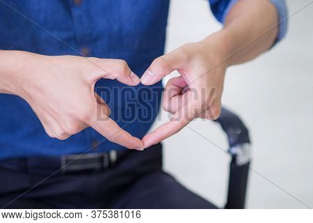 Close-up Of Young Man Making Heart Shape With Fingers. Selective Focus. Concept Of Love And Celebrat