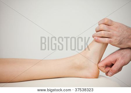 Physiotherapist using his forefinger to massage a foot in a room