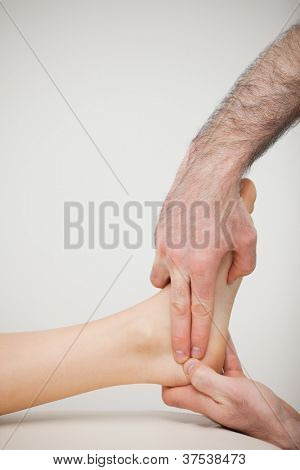 Two fingers pressing the Achilles tendon of a patient in a room