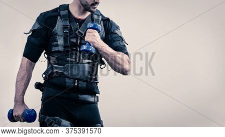 Sporty Man In Electrical Muscular Stimulation Suit Doing Exercise With Dumbbells