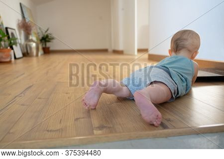Little Baby Lying On Belly On Wooden Floor With Barefoot. Back View Of Adorable Red-haired Infant Cr