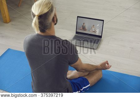 Yoga Online Home. Young Man Following Online Yoga Class And Doing His Morning Meditation Or Breathin