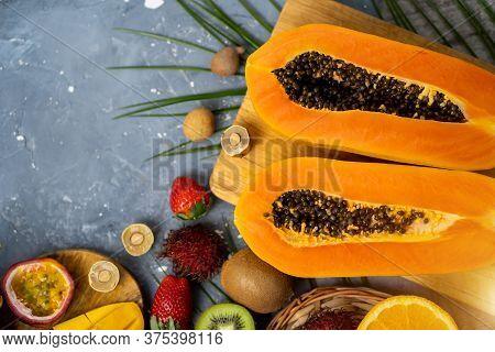 Papaya. Tropical Fruits. Close Up Shot Of Two Halves Of Ripe Papaya With Seeds On Wooden Cutting Boa