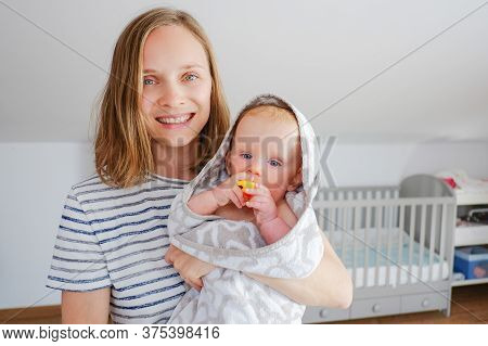 Joyful Mom Looking At Camera And Holding Sweet Dry Baby Wearing Hooded Towel After Shower And Biting