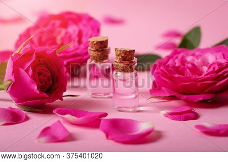 Perfumed Rose Water Or Essential Oil In Glass Bottles With Pink Fresh Rose Flowers And Petals On Pin