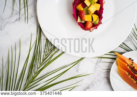 Flat Lay Of Plates With Mixed Fruits And Sliced Fruits. Tropical Fruit Salad Served In Half Dragon F