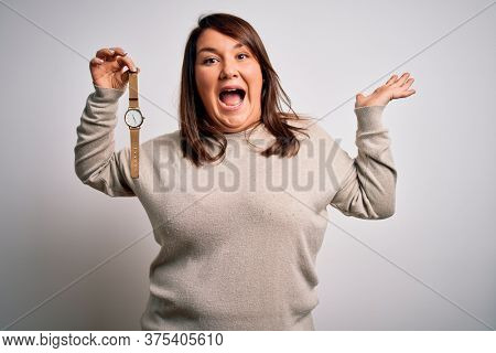 Beautiful brunette plus size woman holding wristwatch over isolated white background very happy and excited, winner expression celebrating victory screaming with big smile and raised hands