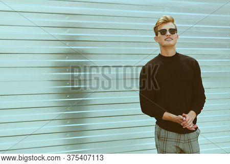 Fashion shot. Handsome positive young man model in black pullover and black sunglasses posing next to fence outdoor. Men's style, beauty. Art portrait.
