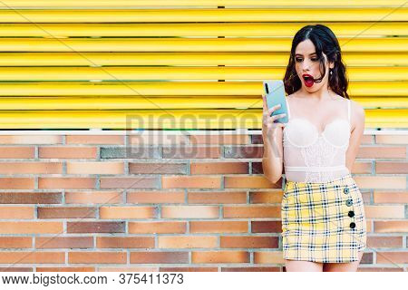 Portrait Of Woman With Open Mouth Looking The Smartphone