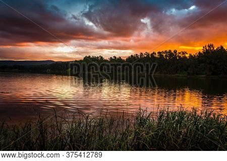 Moody Stormy Clouds And Sunset Over Mountains And River With Foreground Grasses Lining The Riverbank