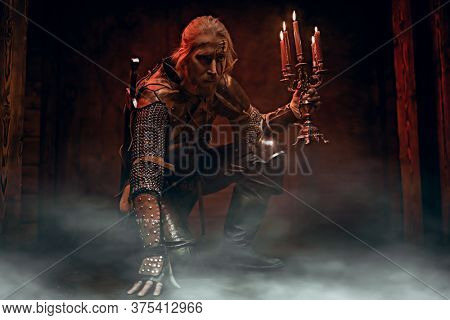 Scenic portrait of a brave medieval warrior in armor and with a sword. The Witcher man.
