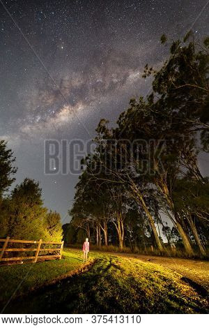 A Casual Dressed Woman Looking Up In Awe Of The Starry Night Sky, The Milky Way Rising And Galactic