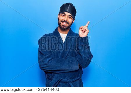 Young hispanic man wearing sleep mask and robe smiling happy pointing with hand and finger to the side