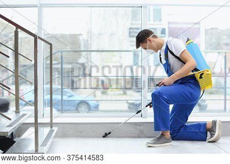 Pest Control Worker Spraying Pesticide Near Window Indoors