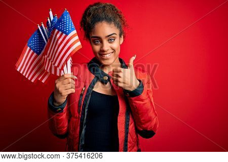 Young african american patriotic girl holding united states flags over isolated red background happy with big smile doing ok sign, thumb up with fingers, excellent sign