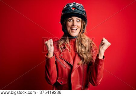 Young beautiful brunette motrocyclist woman wearing moto helmet over red background celebrating surprised and amazed for success with arms raised and open eyes. Winner concept.