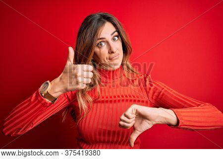 Young beautiful brunette woman wearing casual turtleneck sweater over red background Doing thumbs up and down, disagreement and agreement expression. Crazy conflict