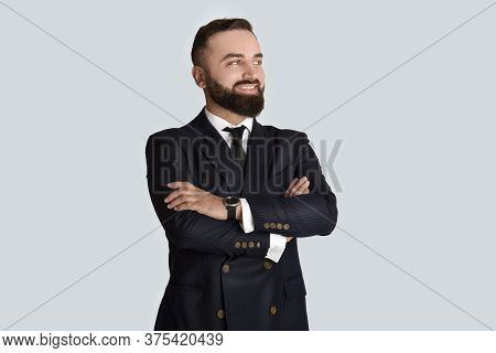 Portrait Of Smiling Businessman In Formalwear With Crossed Arms On Grey Background