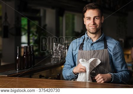 Service At Pub. Attractive Barman Wipes Empty Glass, Standing At Bar In Interior