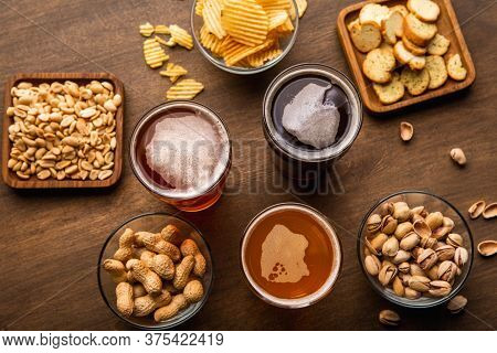 Pint Of Beer For Friends. Craft Drinks In Glasses And Crispy Snacks On Wooden Table, Top View