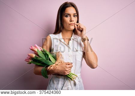 Young beautiful brunette woman holding bouquet of tulips flowers over pink background mouth and lips shut as zip with fingers. Secret and silent, taboo talking