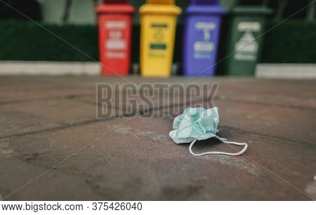 Used Medical Face Mask Discard On Pavement Floor On Blurred Recycle Bin Or Trash. Medical Waste Disp