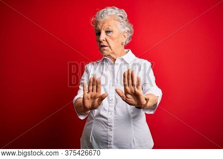 Senior beautiful woman wearing elegant shirt standing over isolated red background Moving away hands palms showing refusal and denial with afraid and disgusting expression. Stop and forbidden.