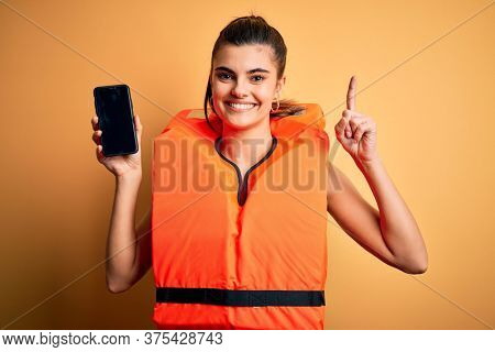 Young beautiful brunette woman wearing safe lifejacket showing smartphone surprised with an idea or question pointing finger with happy face, number one