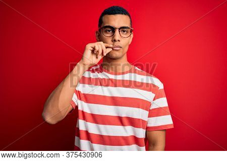 Young handsome african american man wearing casual striped t-shirt and glasses mouth and lips shut as zip with fingers. Secret and silent, taboo talking