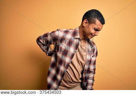 Young handsome african american man wearing casual shirt standing over yellow background Suffering of backache, touching back with hand, muscular pain