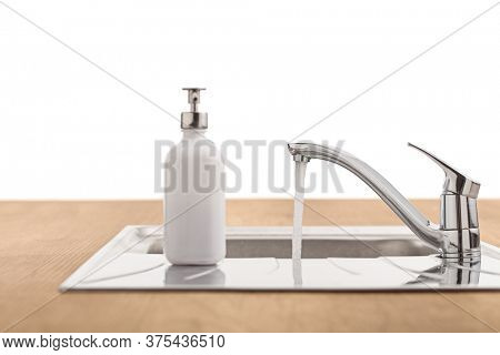 Water running from a tap in a sink with a white soap dispenser isolated on white background