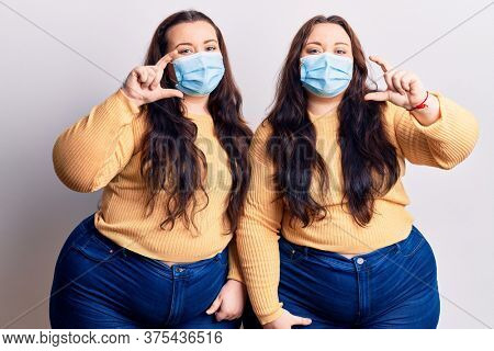 Young plus size twins wearing medical mask smiling and confident gesturing with hand doing small size sign with fingers looking and the camera. measure concept.