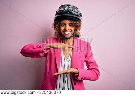 African american motorcyclist woman with curly hair wearing moto helmet over pink background gesturing with hands showing big and large size sign, measure symbol. Smiling looking at the camera