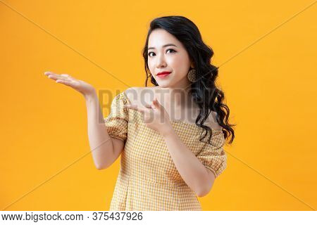 Pretty Lady With Casual Dress Looking Camera With Smile In Studio Advertising For Product