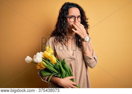 Young beautiful romantic woman with curly hair holding bouquet of yellow tulips smelling something stinky and disgusting, intolerable smell, holding breath with fingers on nose. Bad smell