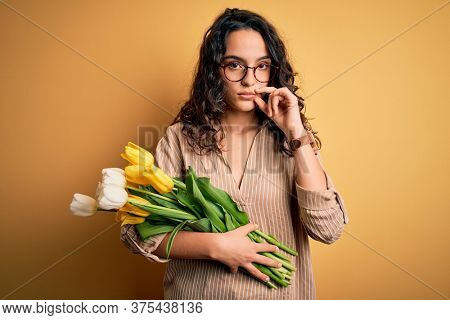 Young beautiful romantic woman with curly hair holding bouquet of yellow tulips mouth and lips shut as zip with fingers. Secret and silent, taboo talking