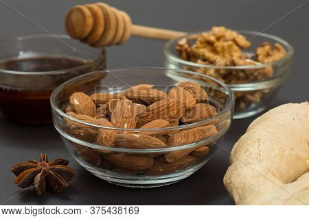 Health Remedy Foods For Cold And Flu Relief With Nuts, Honey, Ginger And A Star Anise On The Black B
