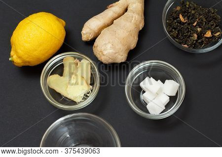 Health Remedy Foods For Cold And Flu Relief With Lemon, Ginger And Green Tea On A Black Background.