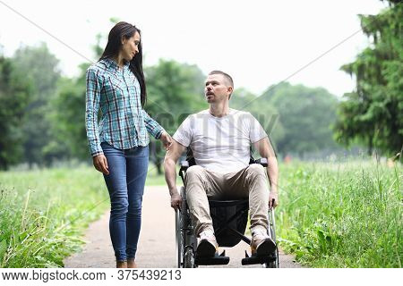 Woman And Man In A Wheelchair Walk In Park And Talk. Walking In Park With People With Disabilities C