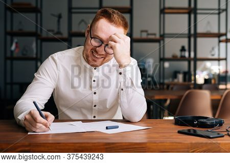 Laughing Happy Composer Wearing Stylish Eyeglasses Is Writing Note Of Song With Pen On Paper Sheet M