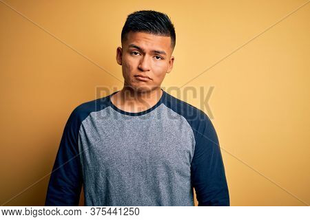 Young handsome latin man wearing casual t-shirt standing over yellow background depressed and worry for distress, crying angry and afraid. Sad expression.