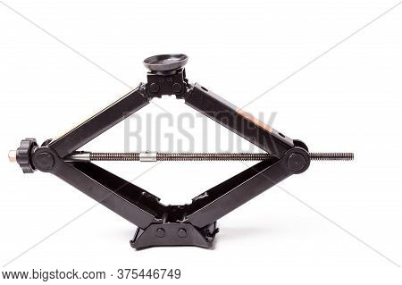 Black Metal Jack On White Background In A Car Service. A Lifting Device That Locks The Car At A Pred